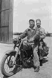 Ground crew on motorcycle near one of Membury's hangars